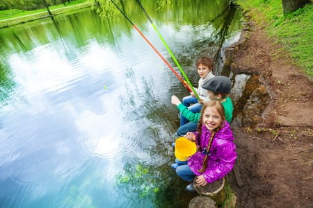 View from up of kids sitting together near the pond holding colorful fishing tackles in beautiful forest landscape 写真素材