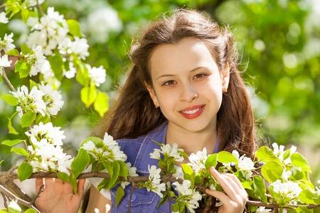 Attractive teenager girl with white flowers on pear tree during sunny summer day in green park Stockfoto