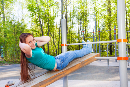 Girl does curls up on the wooden board at the sports ground during summer sunny day outside