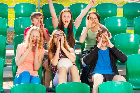Happy teenagers cheer for the team during game at the stadium sitting on the tribune outside in summer Stock Photo