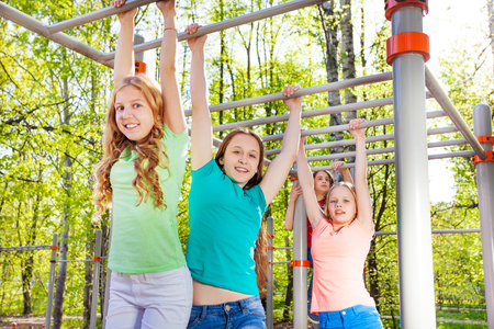 Teenagers hanging on the brachiating bar at the sports ground during summer day with trees on background