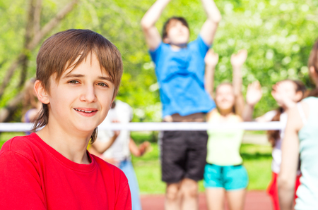Portrait of smiling boy standing on the playground during volleyball game at sunny summer day Stock Photo
