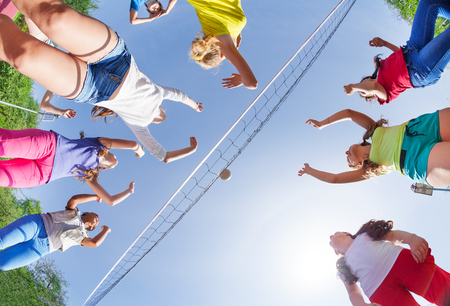 View from below of kids playing volleyball on the game court outside during summer sunny day