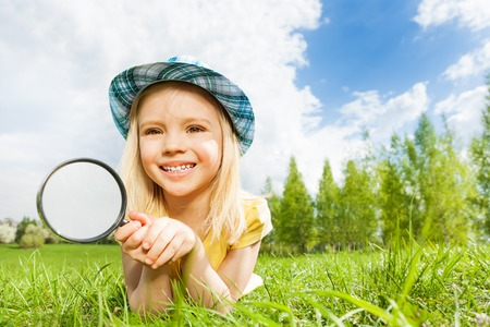 Small beautiful girl with magnifier laying alone  on the green grass during beautiful summer day in park