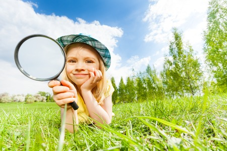 Girl holding magnifier laying alone on the green grass during beautiful summer day in park Stock Photo
