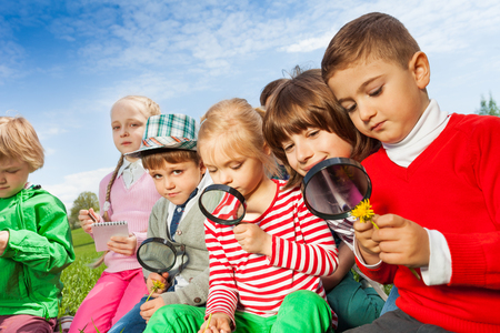 Group of children sitting in the field with magnifier and writing notes in notebook during summer time Stock Photo