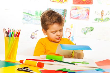 pegamento: Pequeño muchacho lindo que hacer a mano con tijeras, papel y pegamento que se sientan a la mesa con dibujos en el fondo