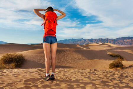 Girl with orange rucksack standing with Death valley view during hot summer day in USA