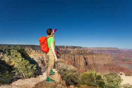 Man with backpack drinks from bottle in Grand Canyon National Park, USA during summer day