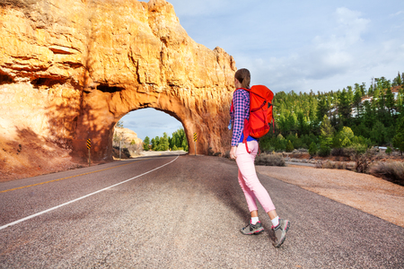 Girl walking on the road with Red canyon view during sunny summer day in USA