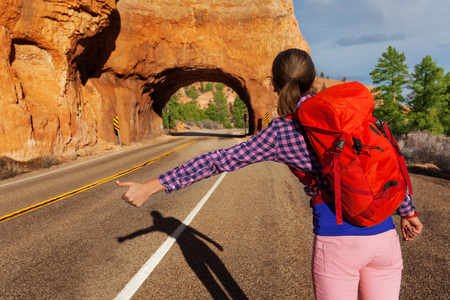 Close-up view of girl with rucksack hitch-hiking on the road near Red canyon during sunny summer day in USA