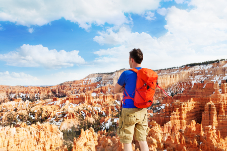 Man with orange rucksack standing with Bryce Canyon National Park view alone Stock Photo