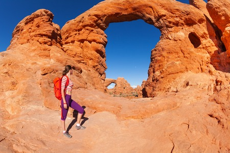 Woman with backpack walking to the beautiful arches Utah during summer day in the USA