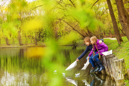Boy and girl near the pond playing with paper boats on the water in beautiful forest landscape