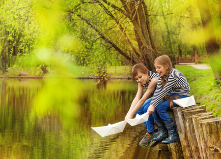 Boy and girl in striped shirts sitting near the pond putting paper boats on the water in beautiful forest landscape