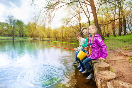Kids sitting together near the pond holding colorful fishing tackles in beautiful forest landscape