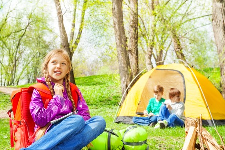Looking girl with red backpack thinks what to write in notebook and kids sitting near the wooden bonfire and yellow tent during camping in summer