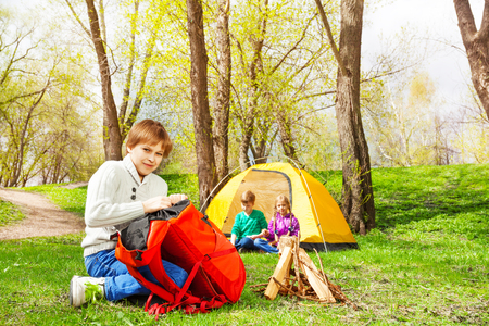 Boy packing the things into red rucksack near the wooden bonfire and his friends sit at yellow tent during camping in summer weather Stock Photo