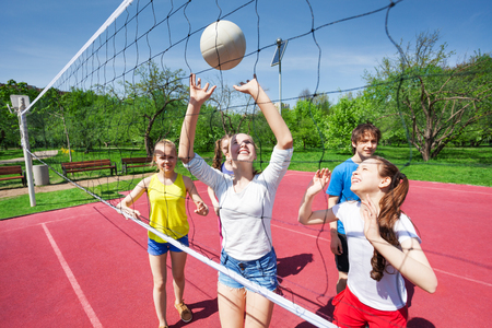 Teens holding arms up and playing volleyball
