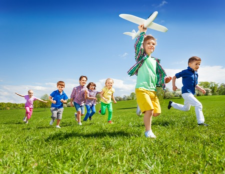Group of active running kids with boy holding big white airplane toy in the field during summer sunny day 写真素材