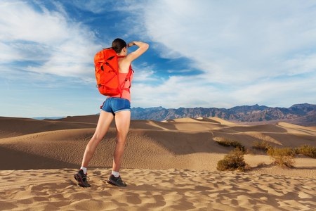 valley view: Girl with orange rucksack looking far and standing with Death valley view during hot summer day in USA