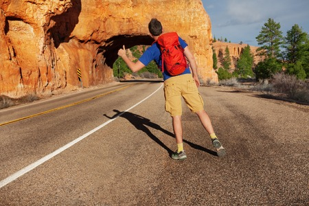 stoned: Hitch-hiking man with rucksack on the road near Red canyon during sunny summer day in USA