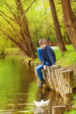 bended: Boy sitting with bended knee near the pond and white paper boat on the water in beautiful forest landscape Stock Photo