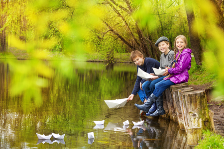 children pond: Smiling friends sitting near the pond putting paper boats on the water in beautiful forest landscape