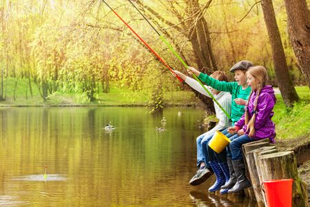 fishing lake: Happy friends sitting and fishing together near the pond with colorful fishrods in beautiful forest landscape