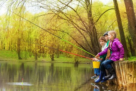 holds: Children sitting and fishing together near the pond with colorful fishrods in beautiful forest landscape