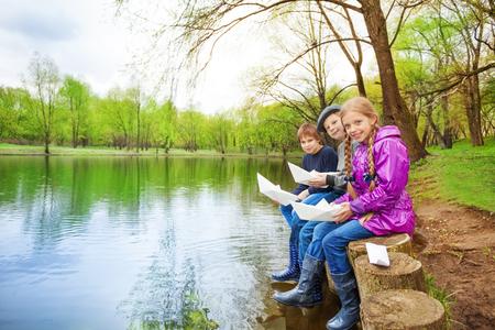 juventud: Amigos sonrientes tienen barcos de papel cerca del río en el hermoso paisaje forestal