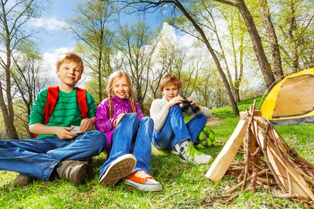 Happy three friends resting together near the wooden bonfire and yellow tent during camping in summer weather Stock Photo