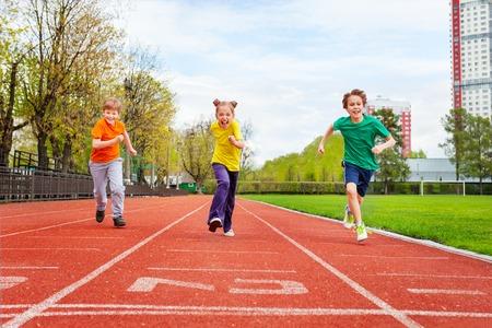 スタジアムでフィニッシュ ライン上にマラソンを走るカラフルなユニフォームの子供たち