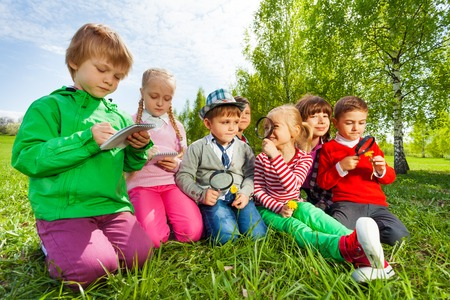 Group of kids sit in the field with magnifier and writing notes in notebook during summer time