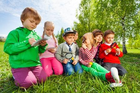 Groep kinderen zitten in het veld met een vergrootglas en het schrijven van notities in de notebook in de zomer