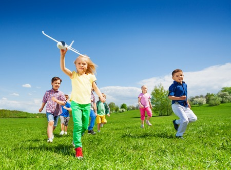many people: Small girl running with kids and holding big white airplane toy in the field during summer sunny day