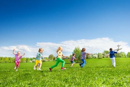 Boy mit Flugzeug Spielzeug und Kinder Reihe während schöne sonnige Wetter im Park hinter ihm her zusammen
