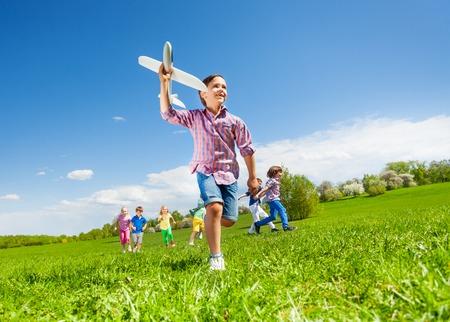 Ansicht von unten Junge mit Flugzeug Spielzeug und Kinder laufen glücklich zusammen im schönen sonnigen Wetter im Park