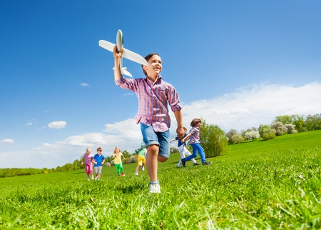View from below of boy with airplane toy and children running happily together during beautiful sunny weather in park