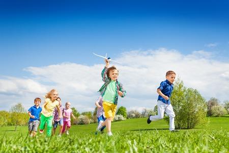 Laufender Junge mit Flugzeug Spielzeug und andere Kinder während der schönen sonnigen Wetter im Park glücklich zusammen
