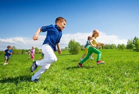 niño corriendo: Felices los niños corriendo en el parque verde durante el día soleado y hermoso clima Foto de archivo