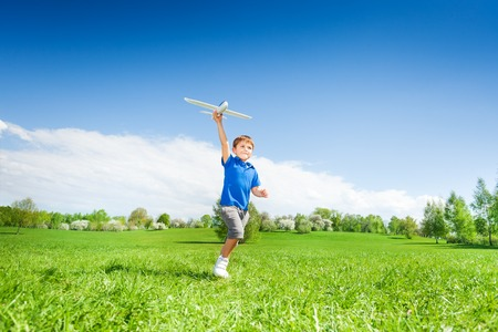 Happy boy holding airplane toy during running in the green meadow during summer day in the park Stock Photo