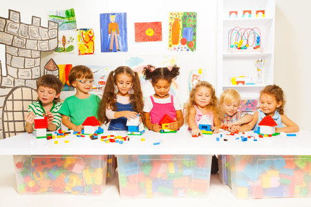 Group of happy kids playing with blocks in kindergarten class constructing simple houses