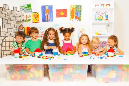 Gruppe glückliche Kinder mit Blöcken in Kindergarten spielen Bau einfachen Häusern