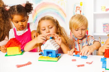 Diverse mooie slimme kinderen jongens en meisjes spelen met plastic blokken bouw van huizen in de kleuterklas Stockfoto