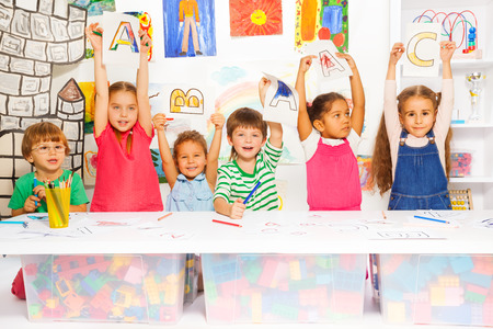 Group of diverse looking children boys and girls in kindergarten class showing letters in early reading class with decoration an paintings on background Foto de archivo