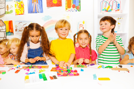 Large group of happy diverse looking preschool kids boys and girls play with plasticine on a lesson Imagens