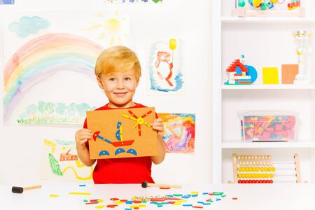 nailed: Handsome little blond boy holding image made of blocks nailed to the plank  with nice little smile