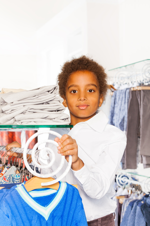 african fashion: Positive African boy standing between rows with clothes on the hangers and glass shelves with piles of clothes in the shopping mall