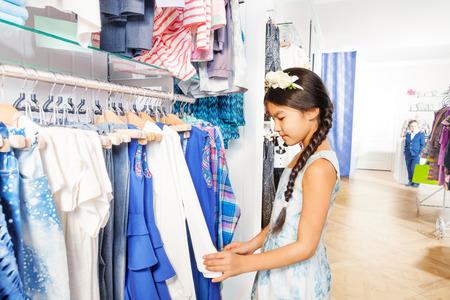 tienda de ropa: Muchacha asiática hermosa con accesorio para el pelo de flores que eligen la ropa en la tienda de ropa